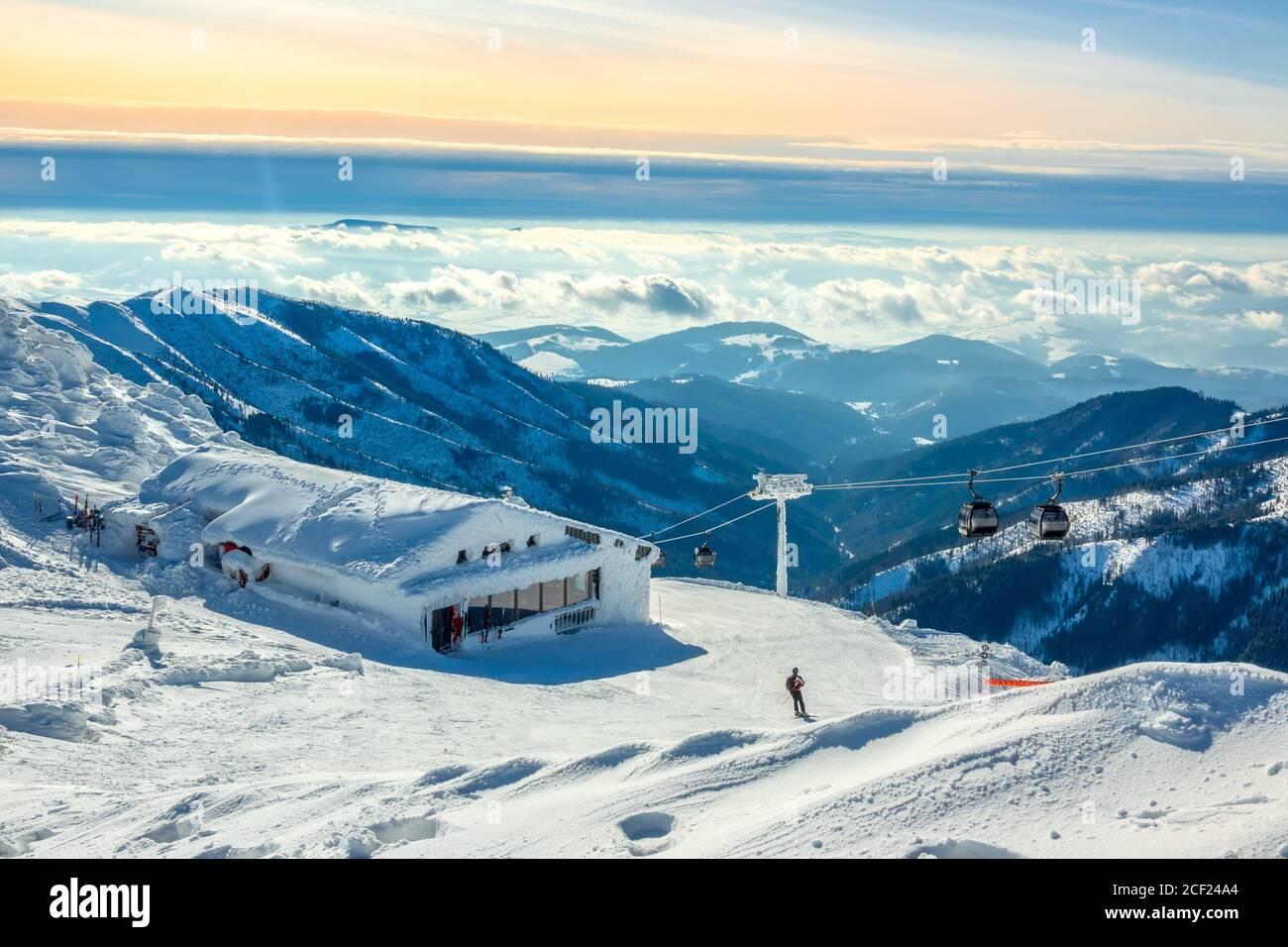 Montañas de invierno. Picos nevados y niebla en los valles. Cielo azul y rosa sobre la pista de esquí. Telesilla y bar. Foto de stock