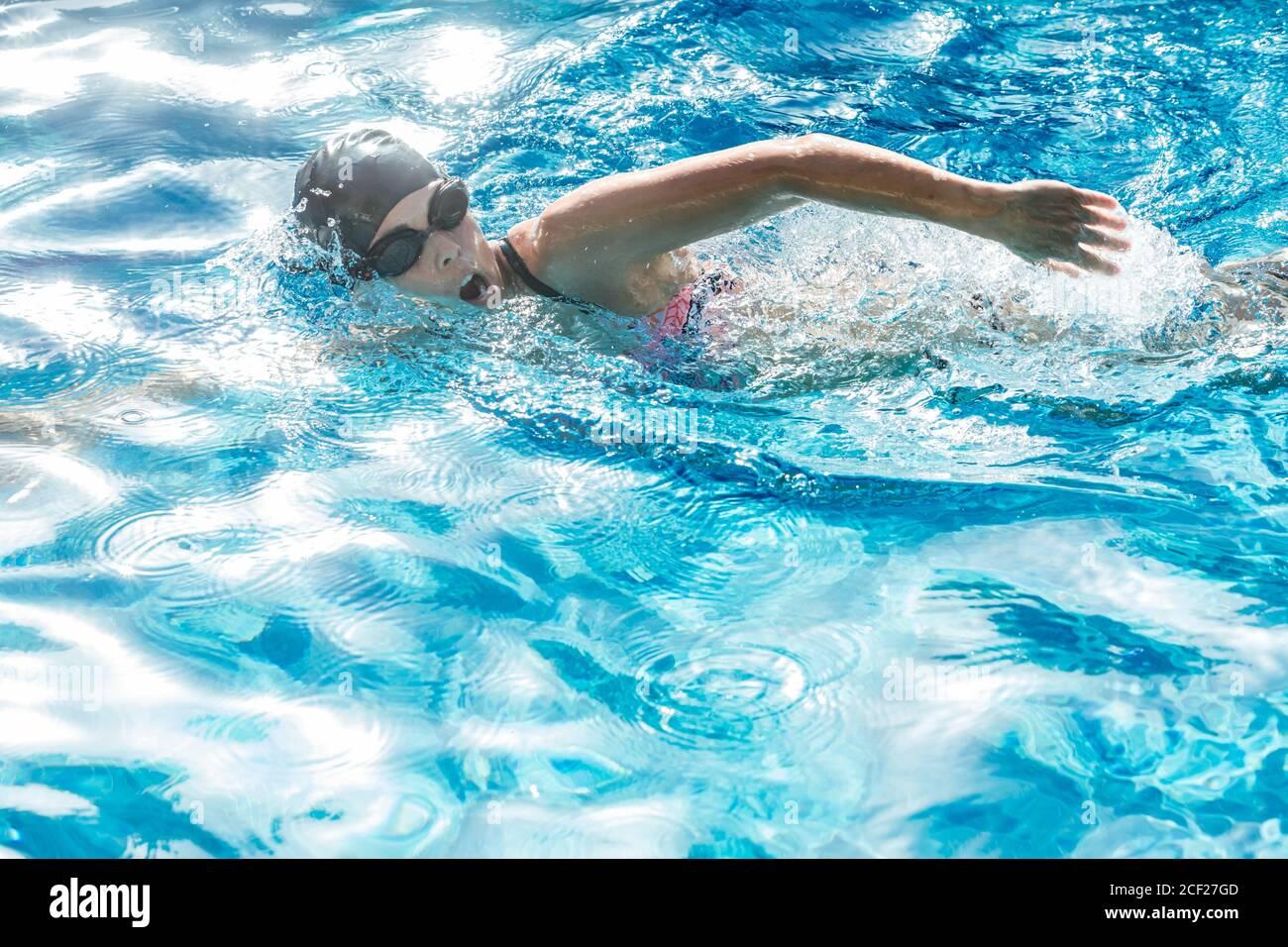 Mujer con gorro de baño y gafas nadando en una piscina. Foto de stock