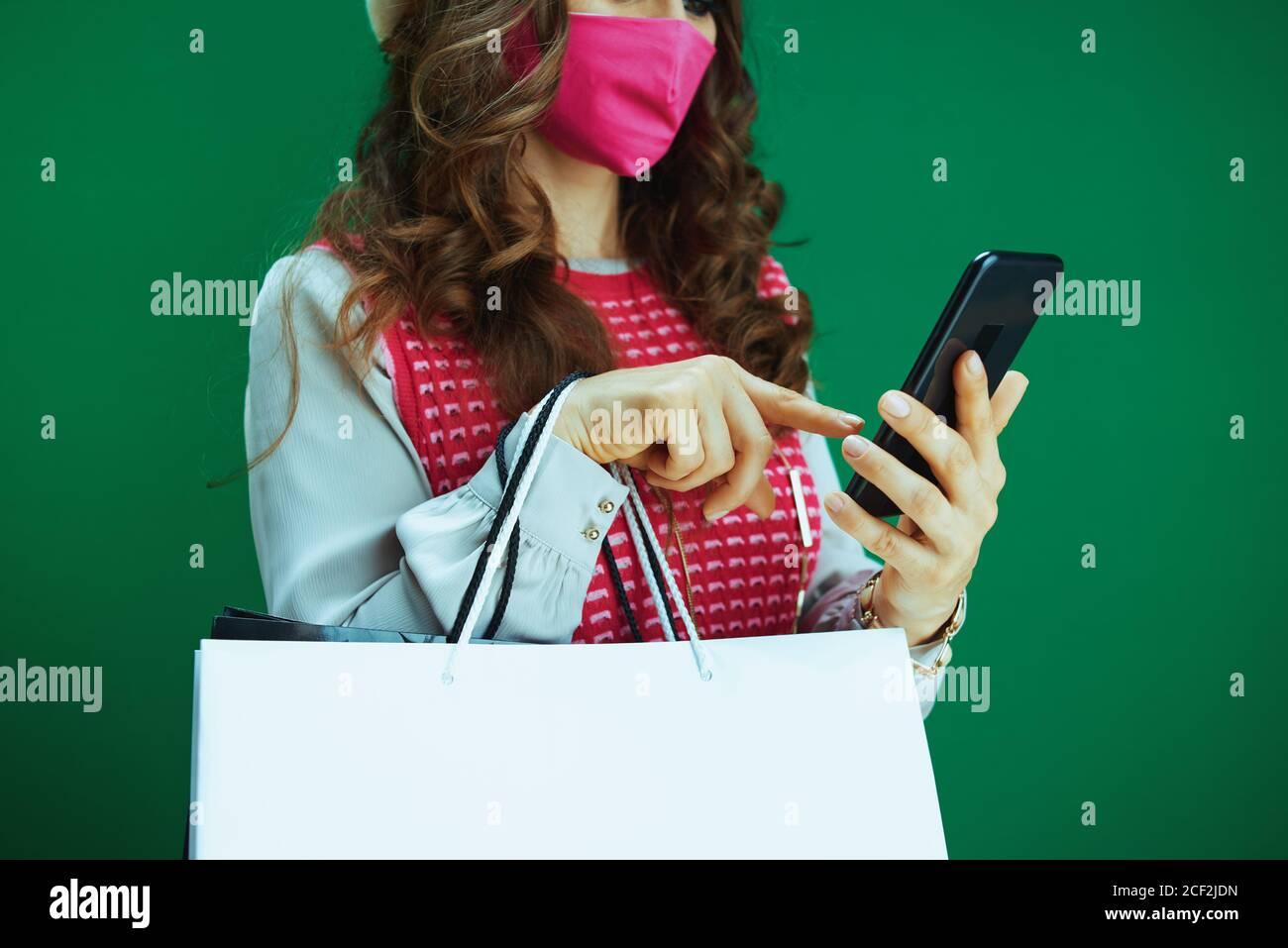 La vida durante la pandemia del coronavirus. Primer plano sobre la mujer comprador en bereta blanca con máscara médica rosa y bolsas de compras comprar en línea en un teléfono inteligente en gr Foto de stock