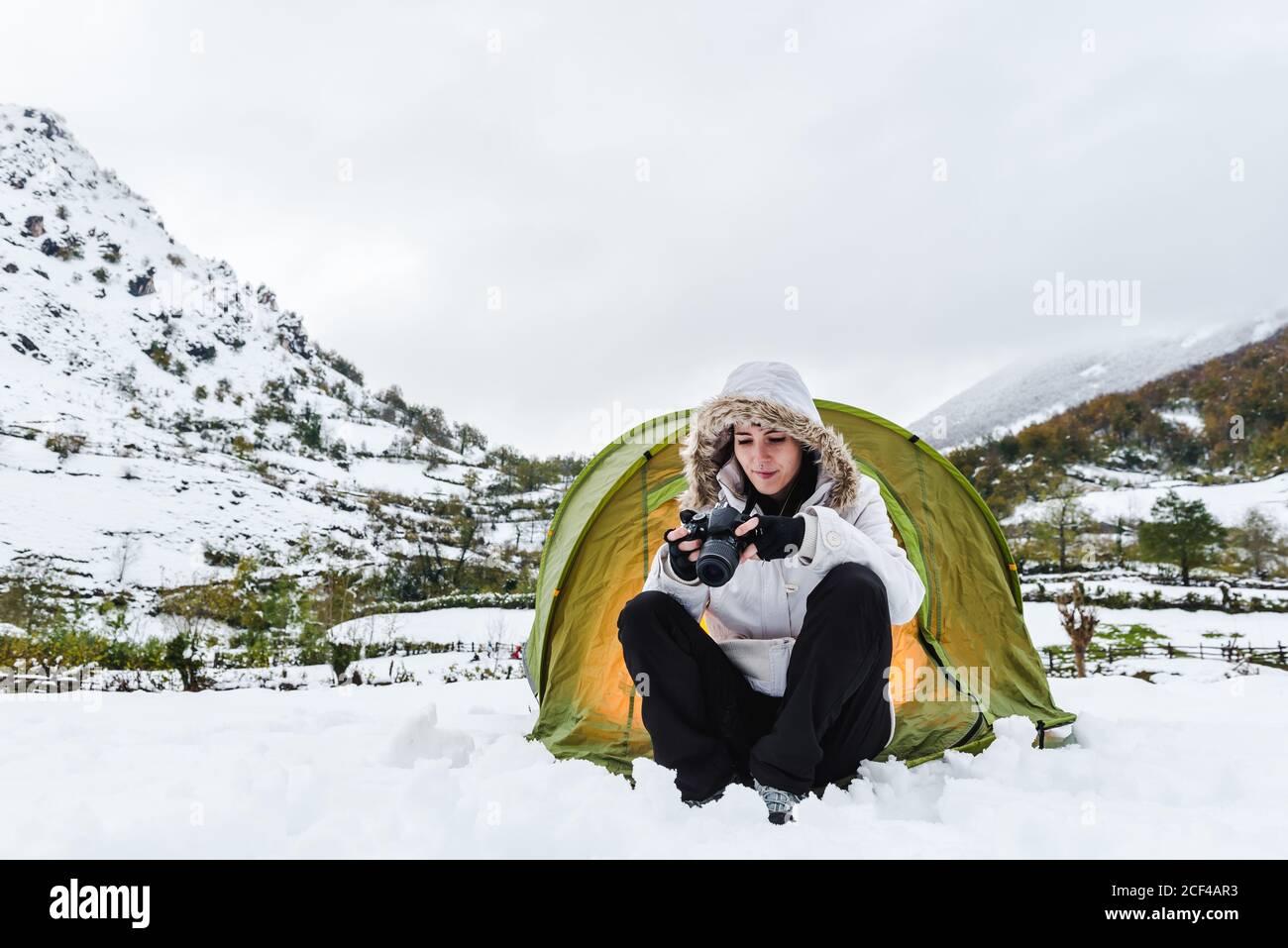 Contenido mujer en blanco chaqueta de invierno y pantalones negros sentado con cámara cerca de verde claro tienda turística en la nieve montañas Foto de stock