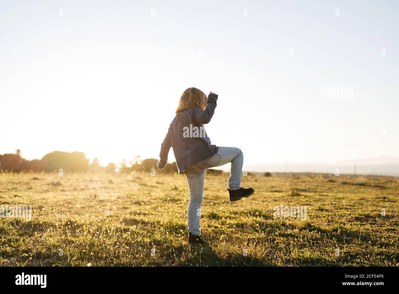 Vista posterior de la adorable chica activa anónima en informal usa jugando y bailando en el campo verde mientras disfrutas de sol noche de verano en el campo Foto de stock