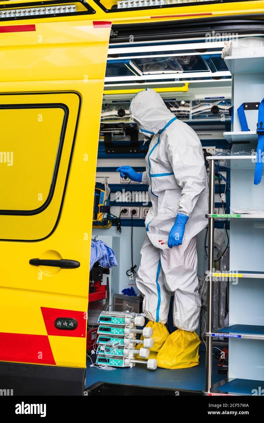 Vista lateral del médico anónimo en traje protector de pie carro de ambulancia cerca de puerta abierta con equipo y examinando al paciente con infección por virus Foto de stock