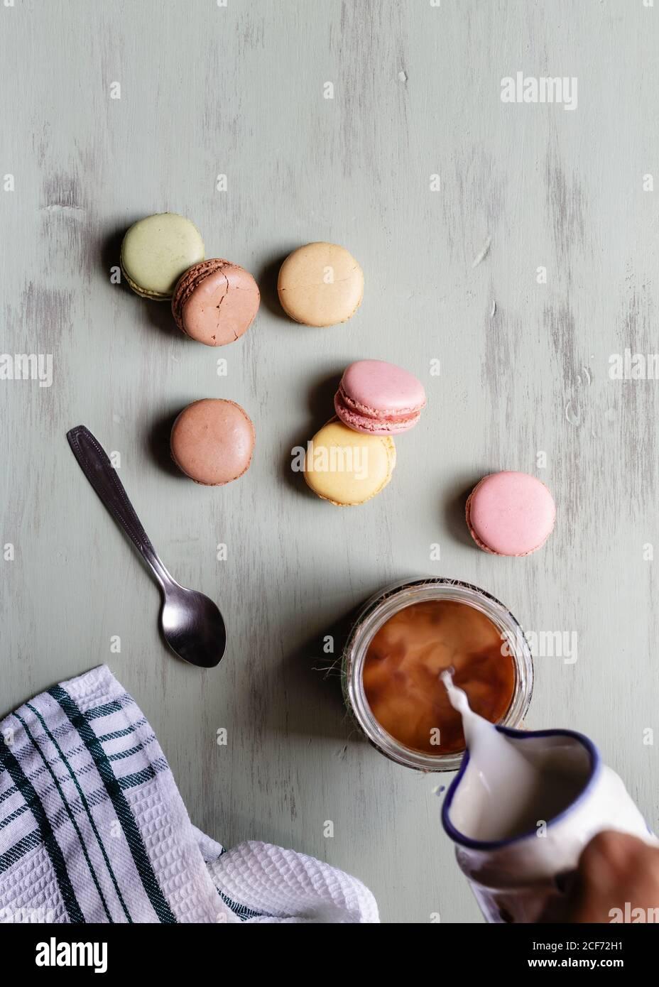 De arriba persona anónima vertiendo leche en taza de café cerca de un montón de coloridos macarrones y cuchara con servilleta mesa blanca Foto de stock