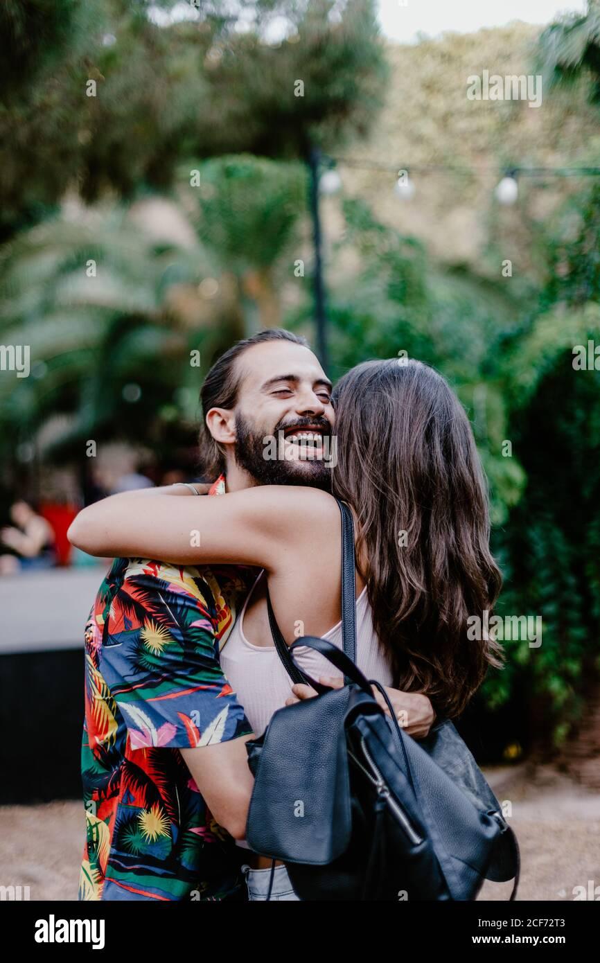 Vista lateral de un hombre con barba y una morena con mochila abrazar con los ojos cerrados sonriendo y de pie mientras abrazaba a los jóvenes morena contra el fondo de las plantas Foto de stock