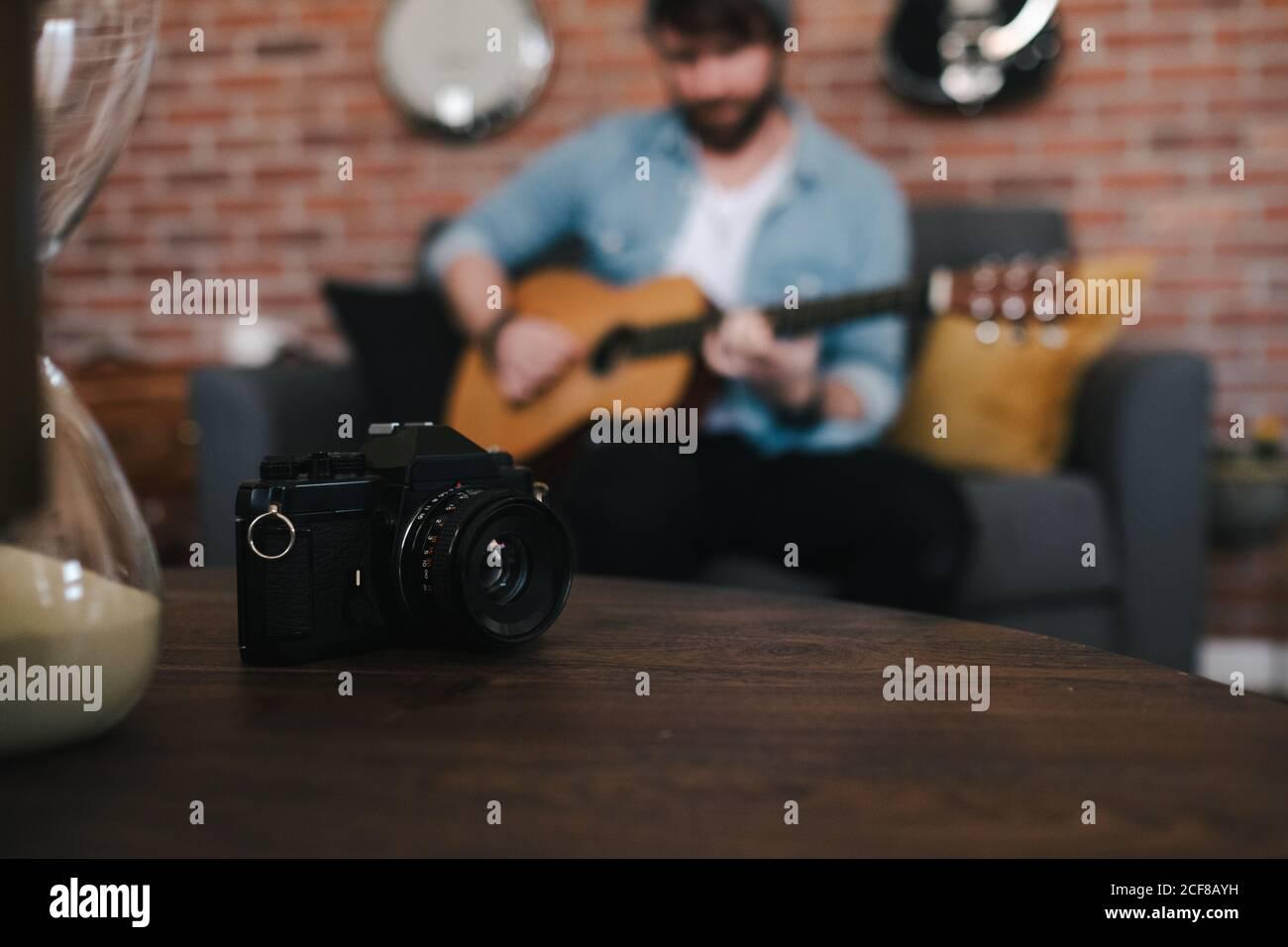 Corta a un tipo con barba en chaqueta de denim tocando la guitarra acústica mientras sentado en un acogedor sofá frente a una mesa de madera con cámara fotográfica y reloj de arena en casa Foto de stock
