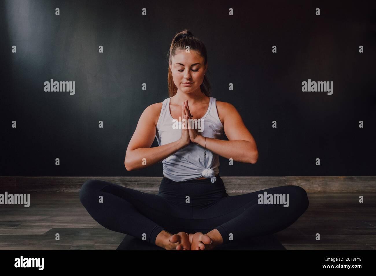 Mujer tranquila y relajada con los ojos cerrados y namaste sentado baddha konasana posición en la alfombra deportiva y concentrarse mientras practica yoga en estudio moderno oscuro Foto de stock