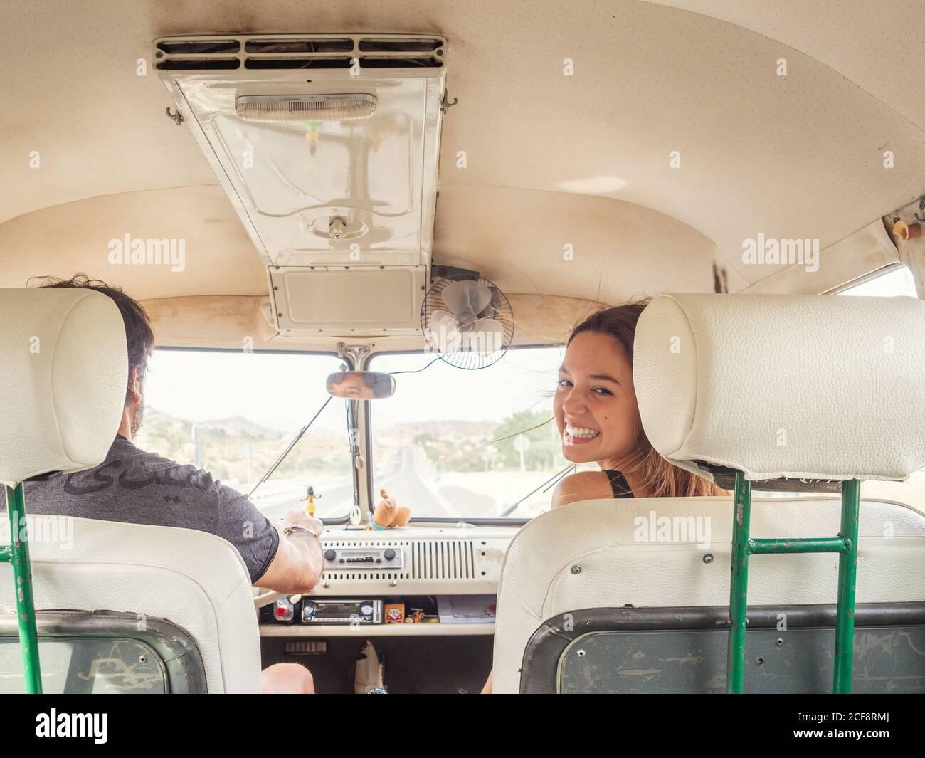 Vista posterior de hombre irreconocible conductor y joven mujer sonriente sentado frente al coche mirando la cámara Foto de stock