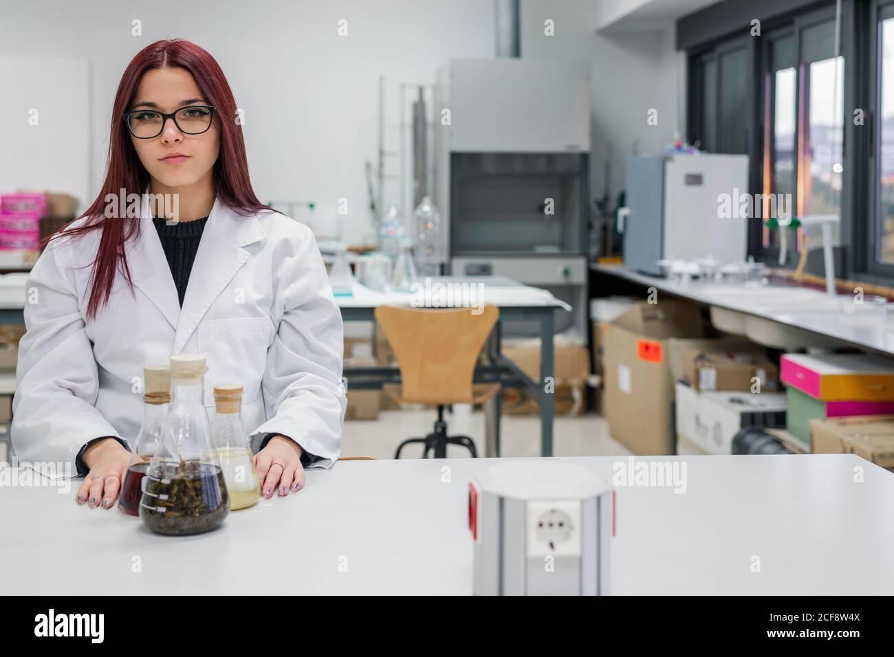 Mujer joven con bata blanca y gafas mirando la cámara mientras se sienta en la mesa con matraces en el laboratorio contemporáneo Foto de stock