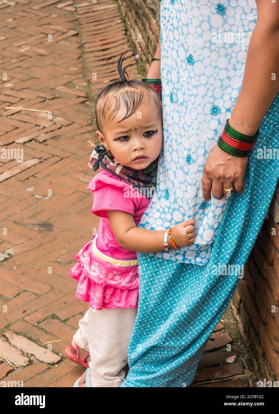 NEPAL, BHAKTAPUR - 19 DE AGOSTO de 2014: Vista lateral del niño pequeño y temeroso de la India que sostiene patas de la cosecha de la madre en la calle Foto de stock