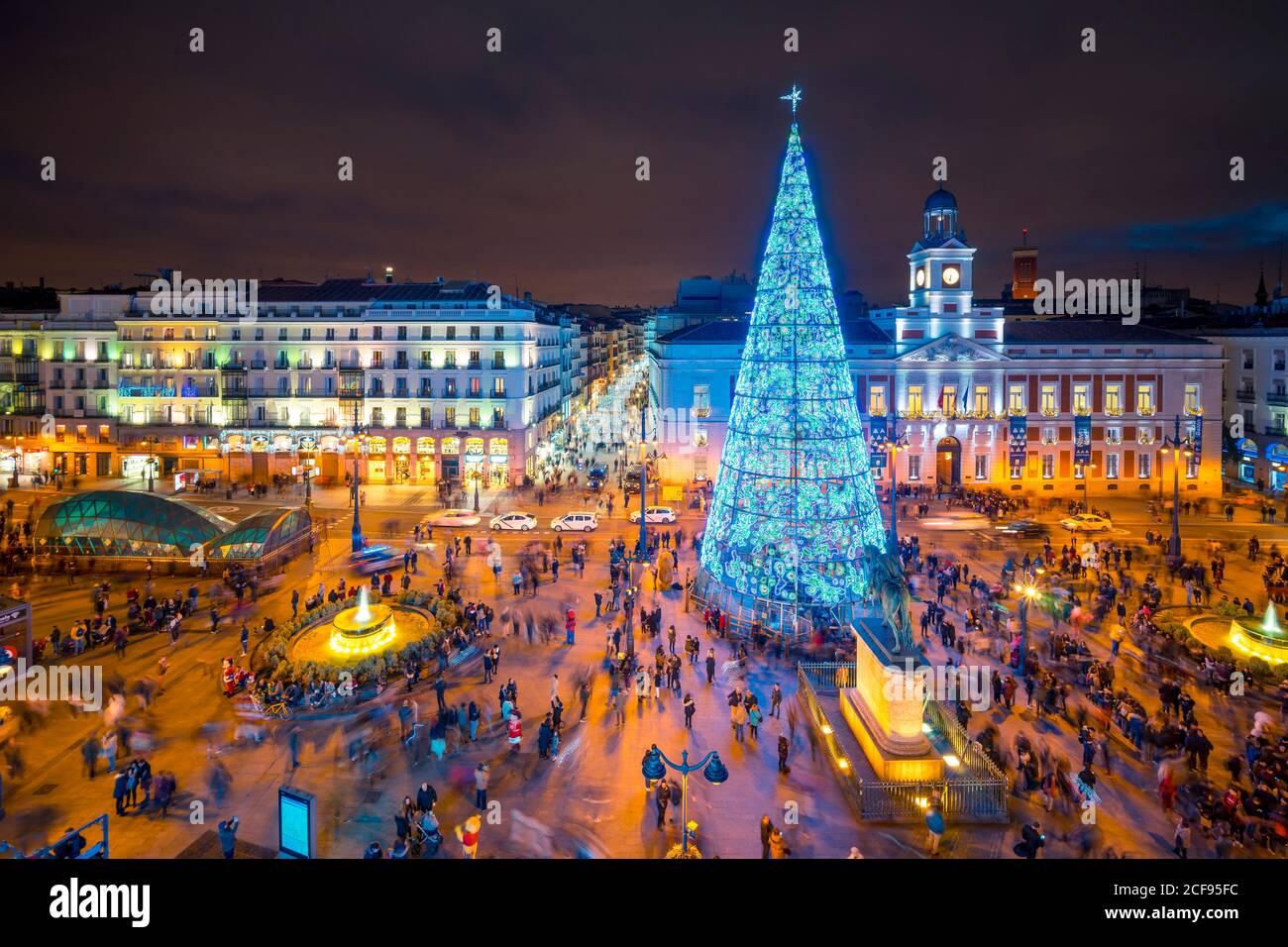 Madrid, España - 19 de diciembre de 2018: Gente disfrutando de la noche de invierno en la plaza de la ciudad Puerta del Sol con árbol de Navidad alto y luminoso decorado con luces azules y edificios iluminados Foto de stock