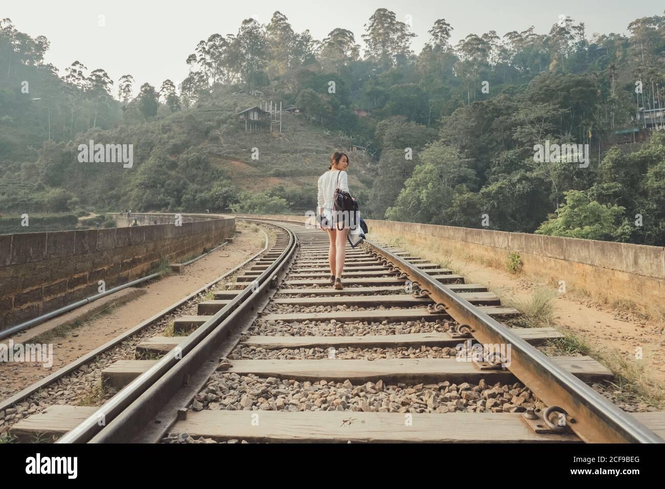 mujer anónima que camina en ferrocarril solitario contra el bosque exótico Foto de stock