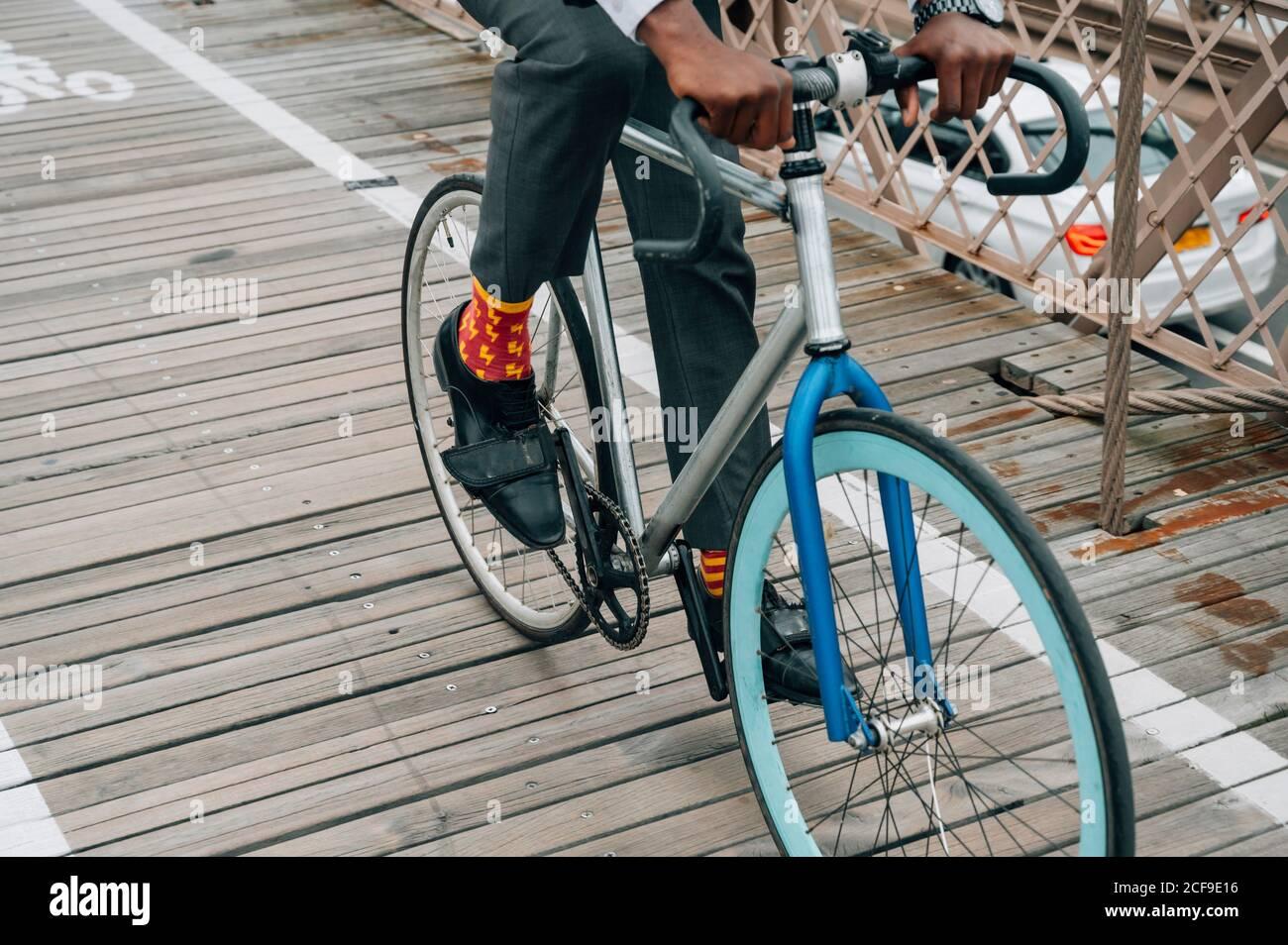Recortada anónimo bien vestido hombre de negocios ciclista en montar en bicicleta Camino de madera entre la estructura de metal rojo con en Nueva York ciudad Foto de stock