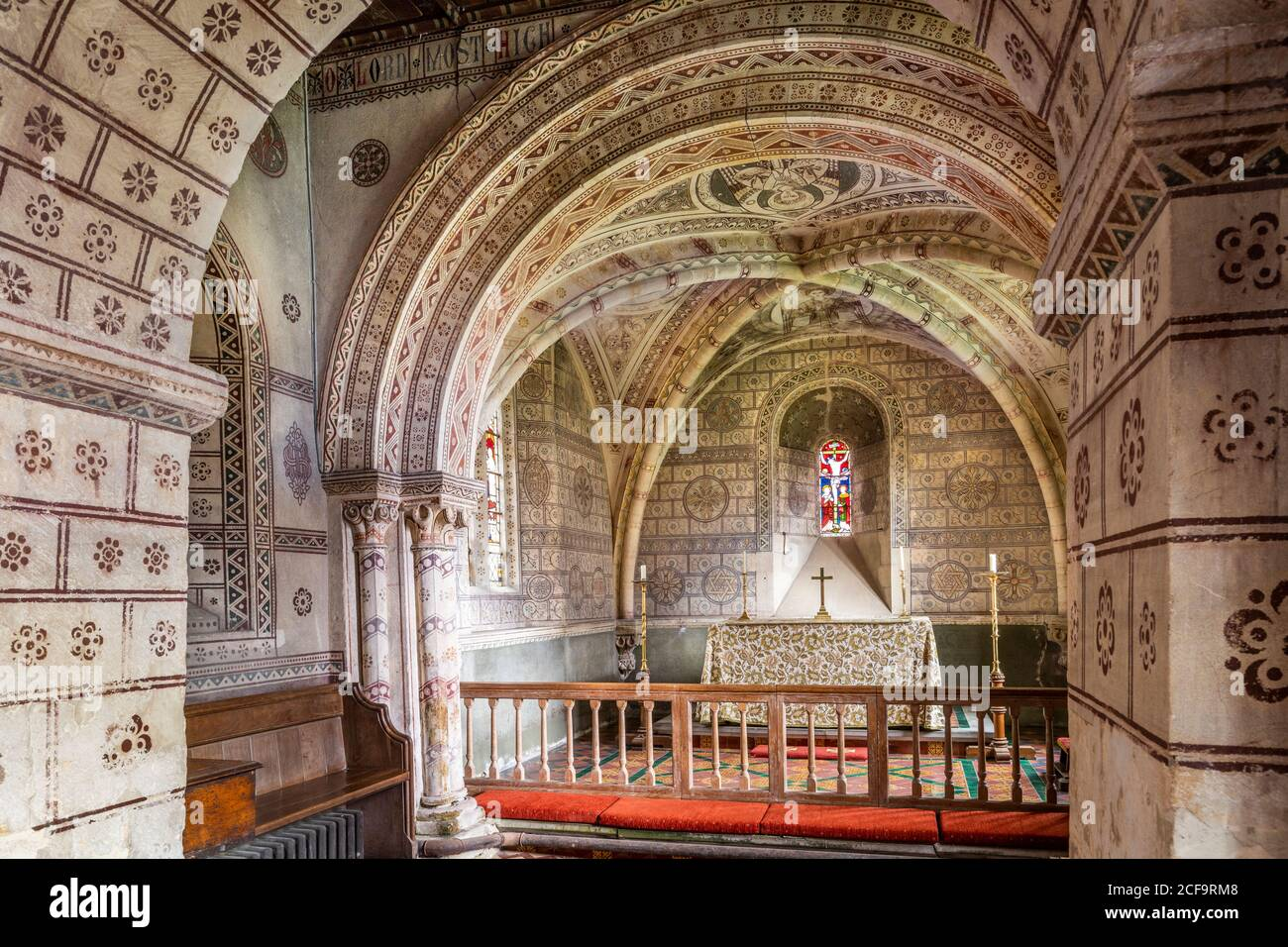La iglesia normanda de San Jorge en el pueblo Cotswold de Hampnet mostrando el coro del siglo 12 decorado en la década de 1870 por el vicario en ese momento. Foto de stock