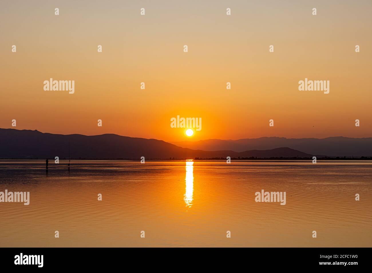 Sol anaranjado bajando detrás de colinas oscuras reflejando en paz el agua ligeramente ondulada crea un paisaje marino romántico Foto de stock