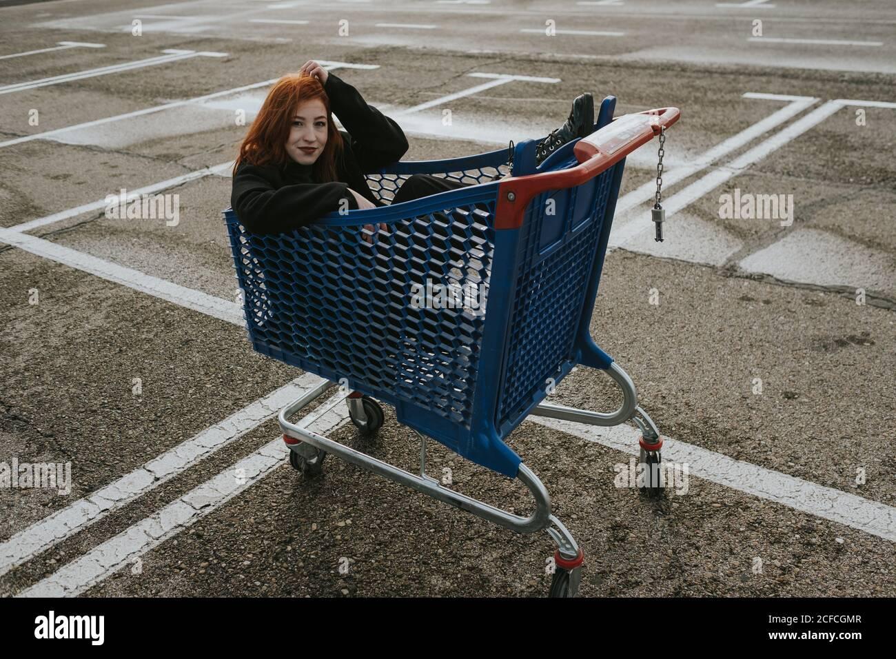 Mujer joven atractiva con pelo rojo en chaqueta negra teniendo diversión sentado en el carrito de compras en el estacionamiento marcado Foto de stock