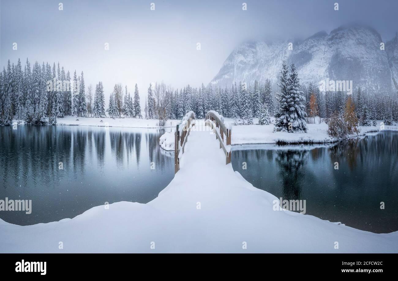 Hermoso paisaje canadiense de invierno con puente cubierto de nieve sobre la calma agua con bosque de abetos y montañas nevadas en el fondo Foto de stock