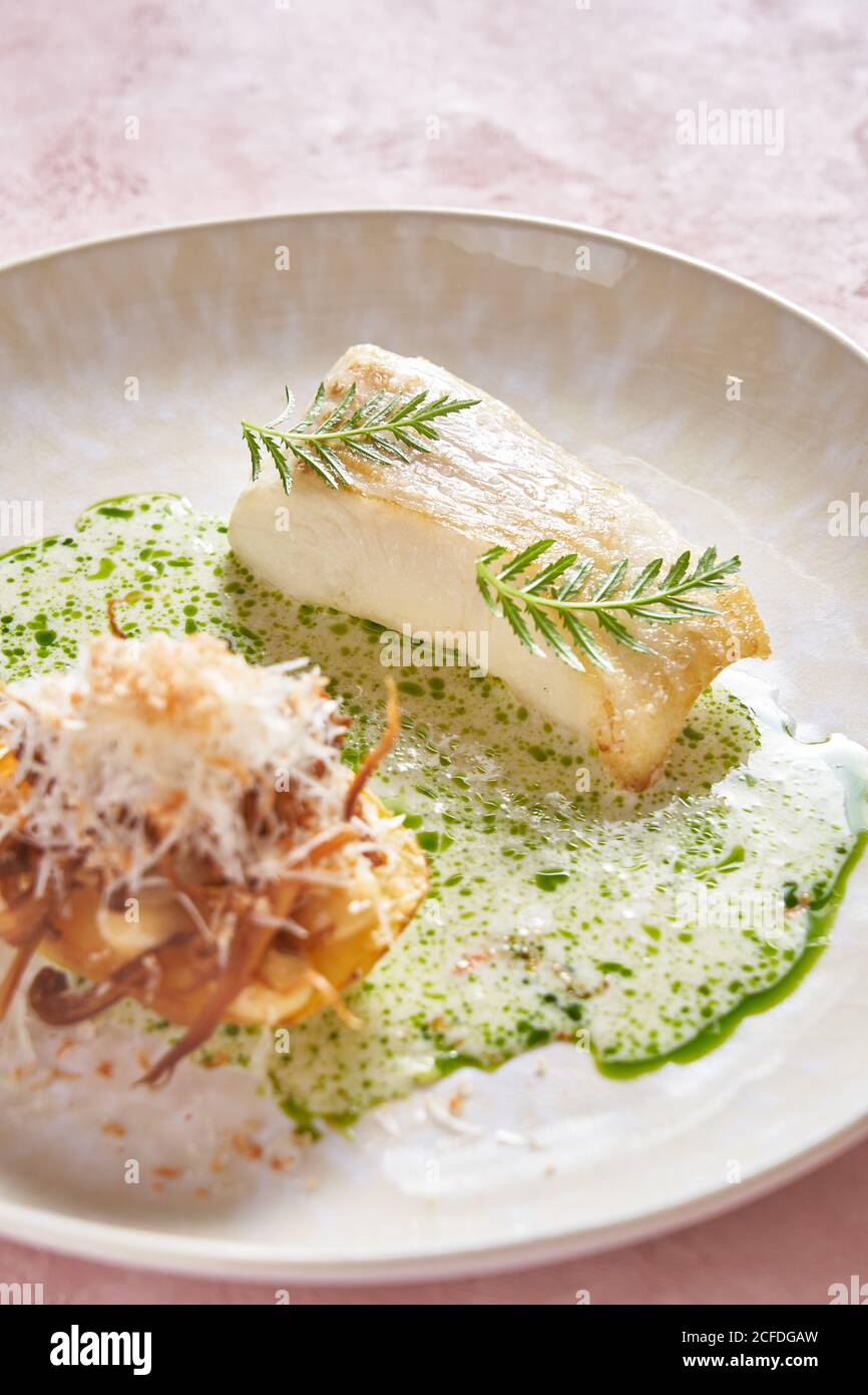 Salsa de crema a plato de pescado delicioso con hierba sobre rosa fondo en el restaurante Foto de stock