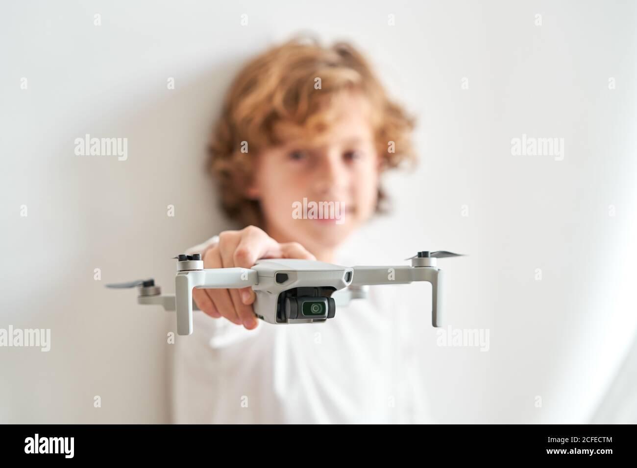 Niño manipulando un drone y el mando a distancia que acaba de dar a él Foto de stock