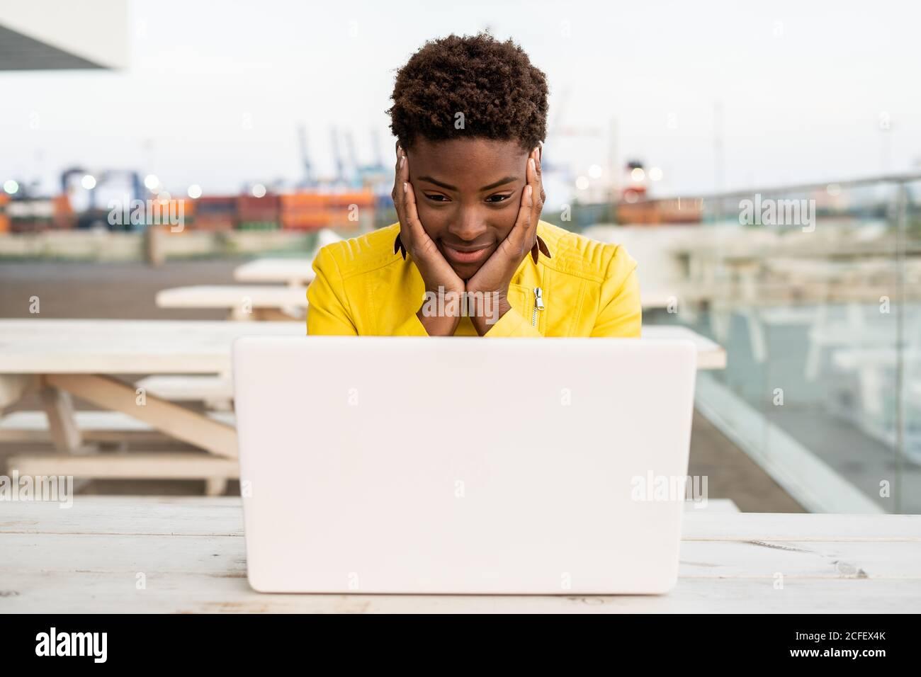Cara sorprendida de una mujer negra afroamericana con chaqueta amarilla usando un ordenador portátil en un escritorio de madera en la ciudad sobre fondo borroso Foto de stock