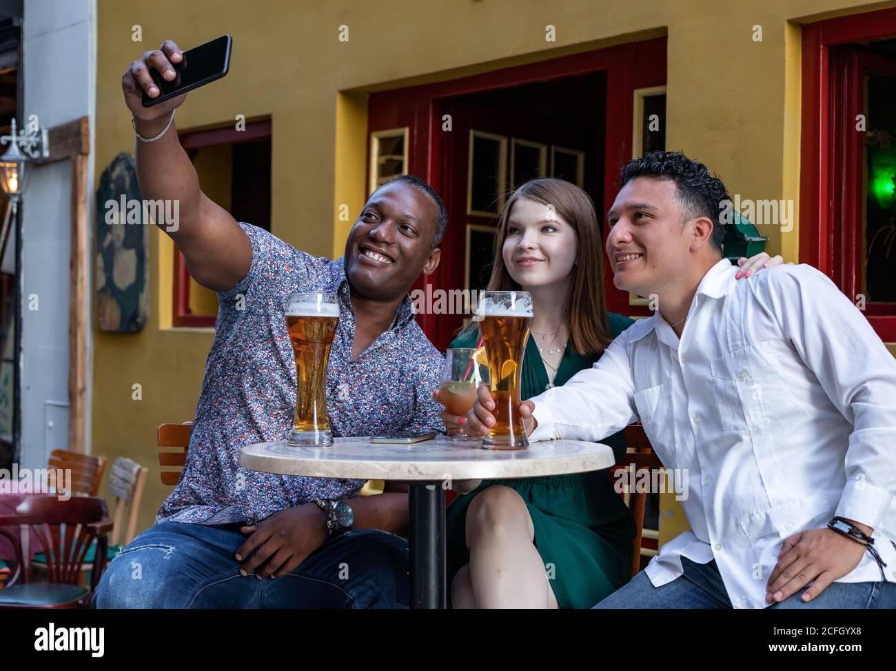 Grupo multirracial de amigos bebiendo y tomando selfie en la terraza de la calle del café. Concepto de amistad con jóvenes multiétnicos disfrutando del tiempo Foto de stock