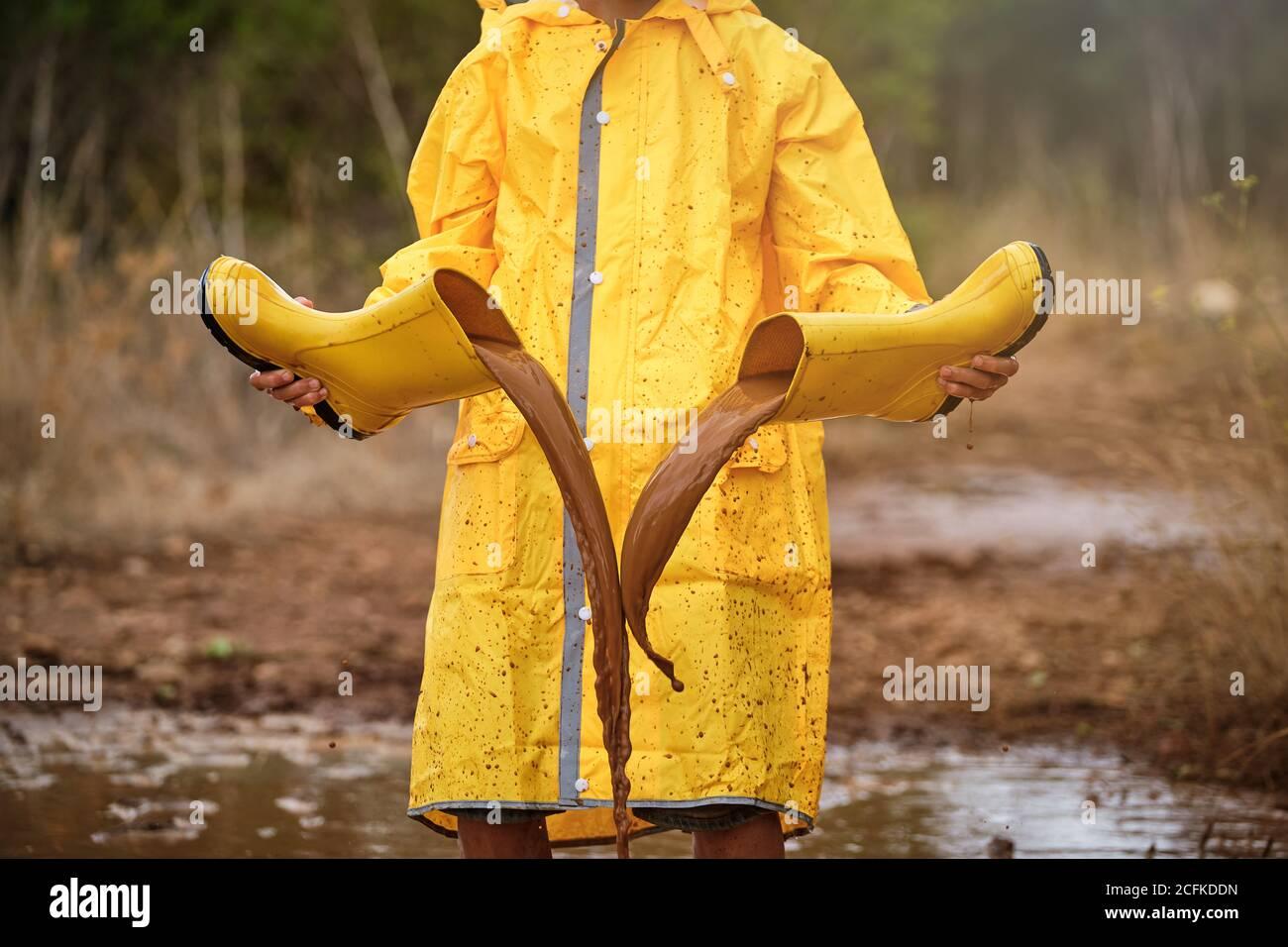 Persona con impermeable amarillo jugando con las botas de agua llenarlos con agua de un charco y vaciarlos en medio del bosque Foto de stock