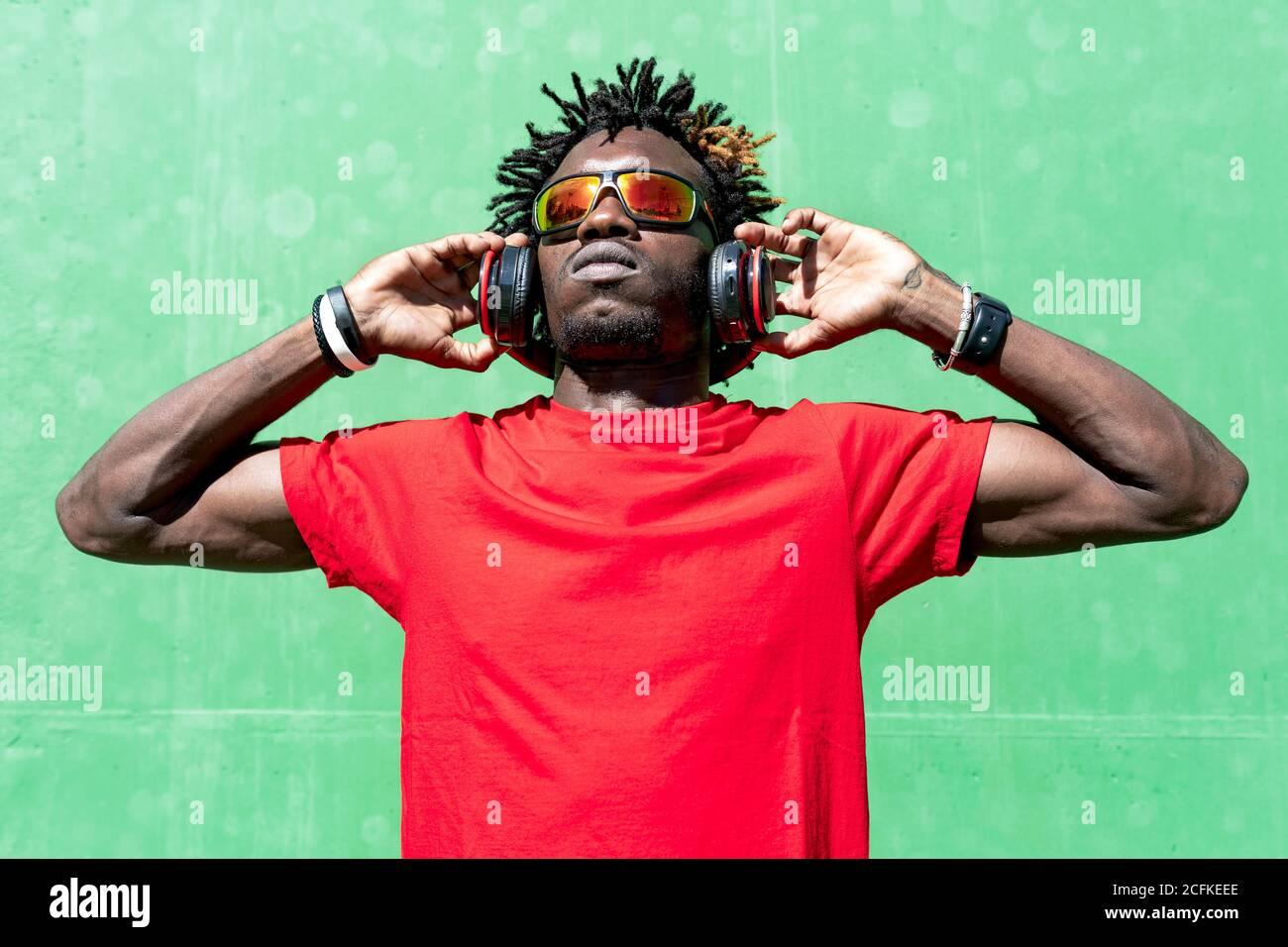 Atleta afroamericano masculino en ropa deportiva y con auriculares relajante en la calle después de entrenar en el día soleado mientras se está mirando Foto de stock