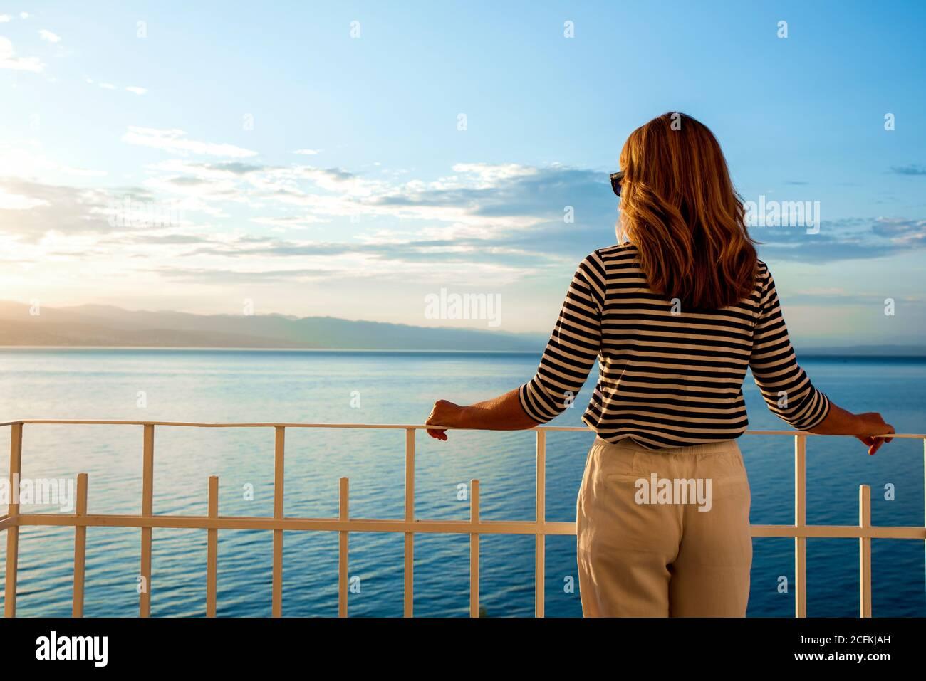 Un tiro de mujer bonita con sombrero de paja y gafas de sol mientras estaba de pie en el balcón y mirando a la vista al mar. Soñando despierto. Foto de stock