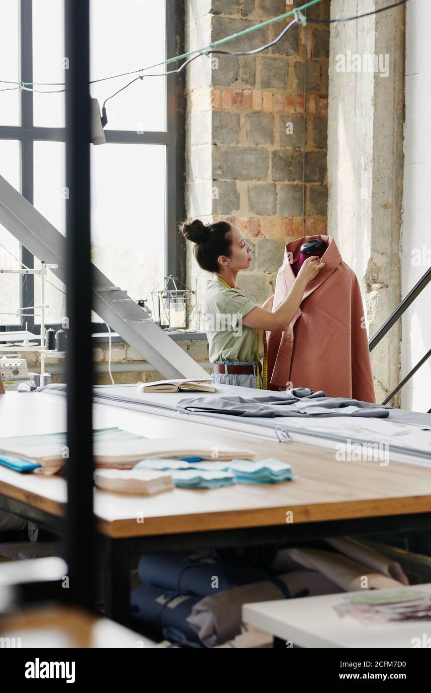Mujer trabajadora de moda moderna diseño de ropa de costura de estudio en falso Foto de stock