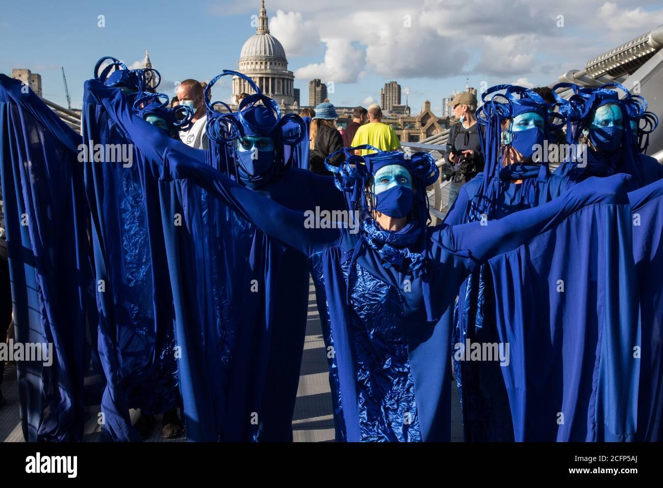 Londres, Reino Unido. 6 de septiembre de 2020. Los rebeldes azules cruzan el Puente del Milenio con otros activistas climáticos de la Rebelión del Océano y la Rebelión de extinción durante una colorida marcha de extinción Marina. Los activistas, que asisten a una serie de protestas de la Rebelión de septiembre en todo el Reino Unido, están exigiendo protecciones ambientales para los océanos y pidiendo el fin de la inacción gubernamental global para salvar los mares. Crédito: Mark Kerrison/Alamy Live News Foto de stock