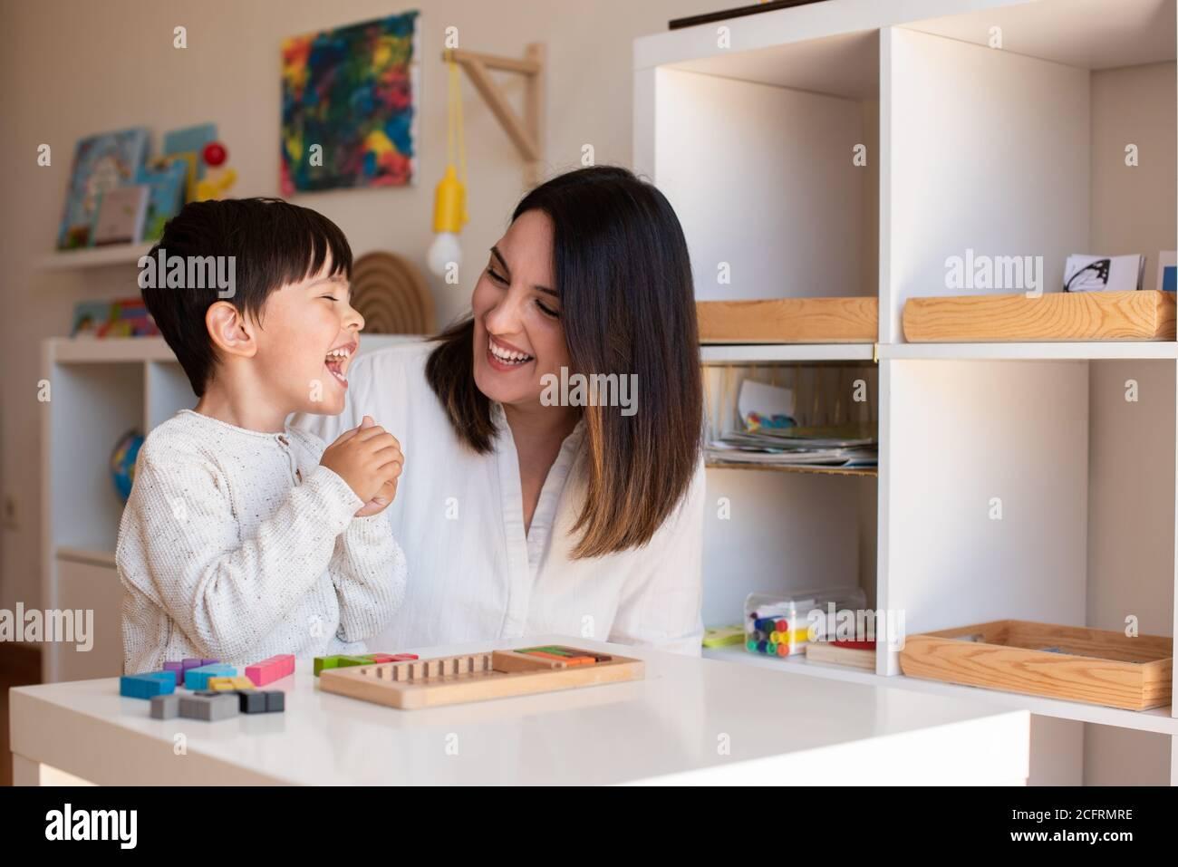 Lillte Kid jugando con un rompecabezas de madera de tetris y ayuda de madre o maestro. Resolución de problemas en casa. Comunidad de aprendizaje. Escuela Montessori Foto de stock