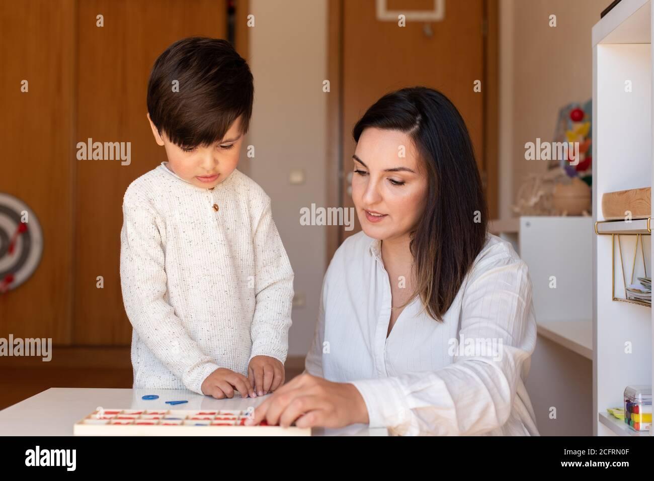 Lillte Kid aprendiendo a escribir y leer con un alfabeto y la ayuda de la madre o del maestro. Resolución de problemas en casa. Comunidad de aprendizaje. Escuela Montessori Foto de stock