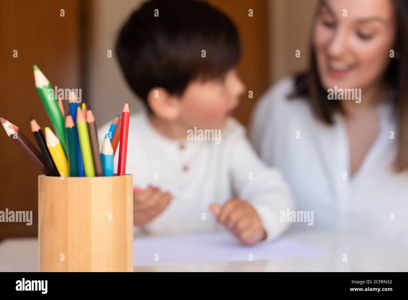 Pequeño niño de preescolar dibujo con lápices de colores con madre o maestro educador. Céntrese en los lápices. Homeschooling. Comunidad de aprendizaje. Montess Foto de stock