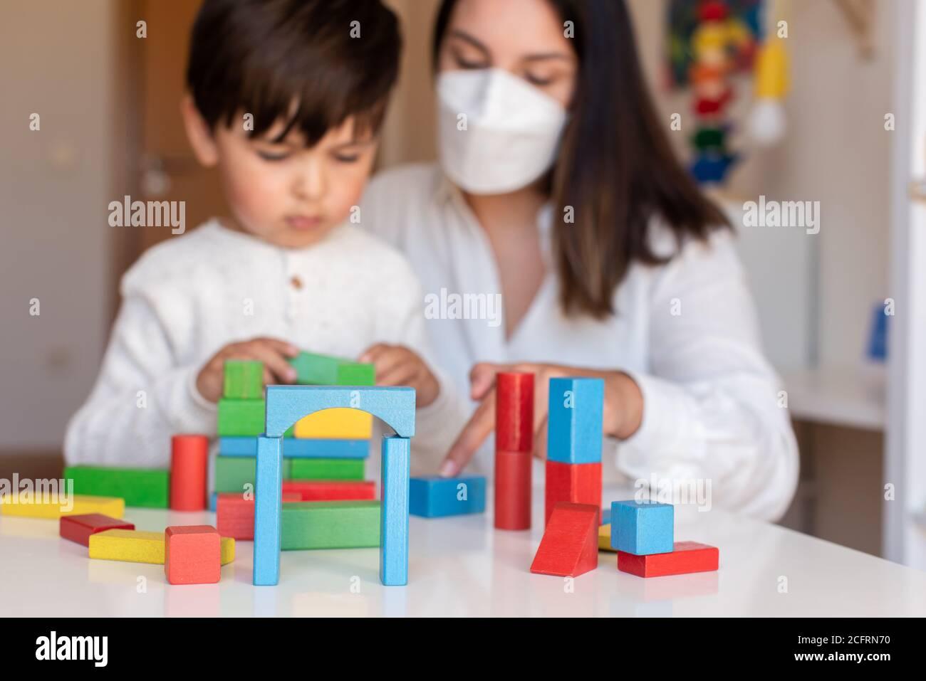 Liltle Preschooler Kid jugando con bloques de madera y maestro educador ayuda a usar la máscara para la pandemia del coronavirus. Resolución de problemas en casa. Comunidad de aprendizaje. Foto de stock