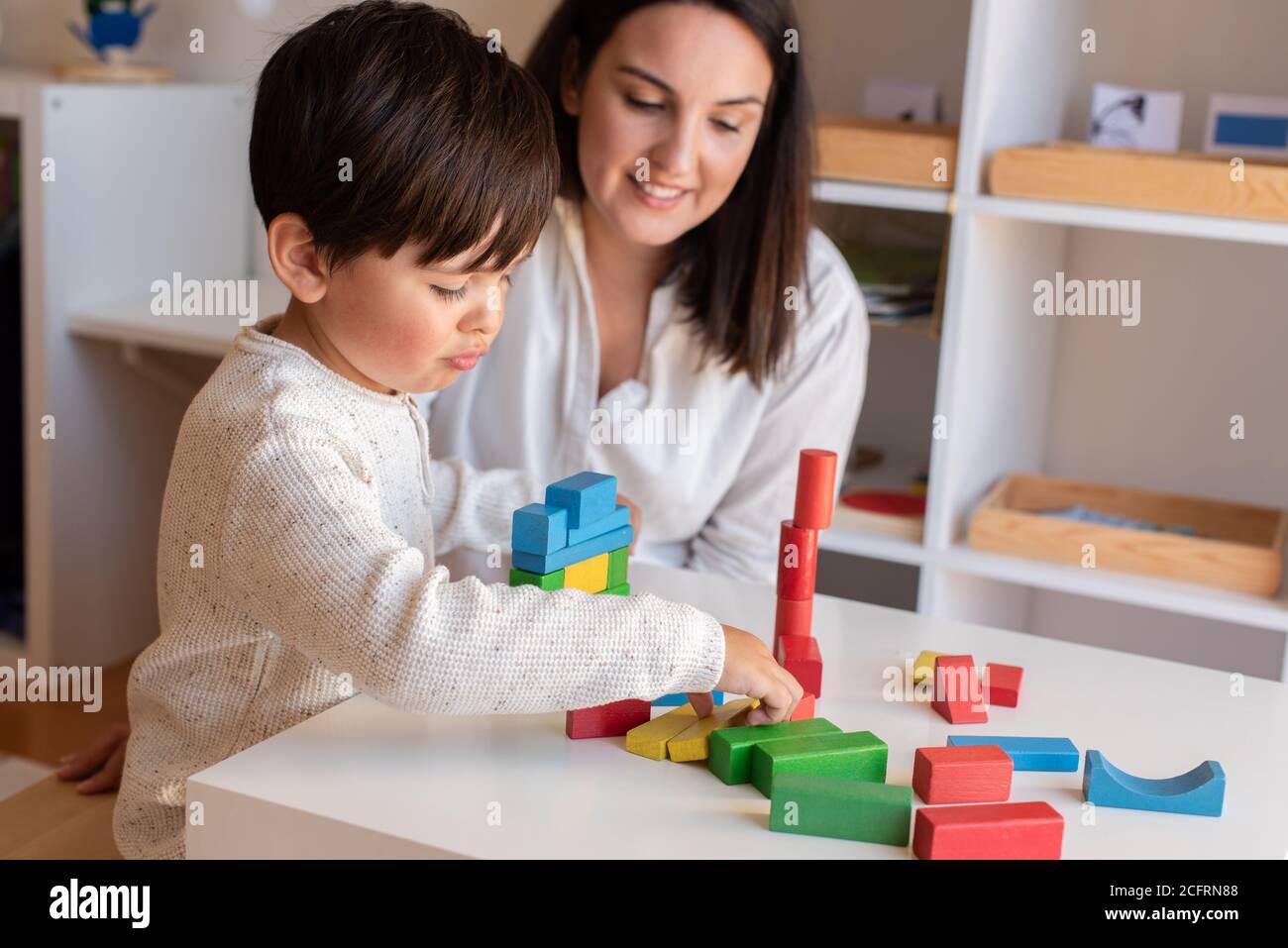 Liltle Preschooler Kid jugando con bloques de madera y la maestra educador ayuda. Resolución de problemas en casa. Comunidad de aprendizaje. Escuela Montessori Foto de stock