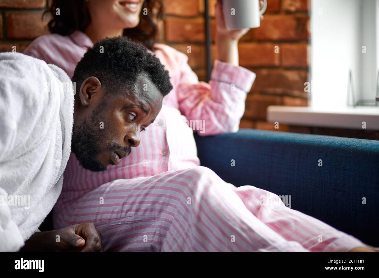 hermosa mujer embarazada y su guapo marido afro escuchando al bebé en el vientre, pasando tiempo juntos en casa Foto de stock