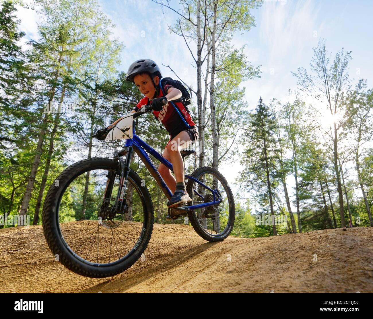 Un niño pequeño (8 años) saltando en su bicicleta de montaña Foto de stock