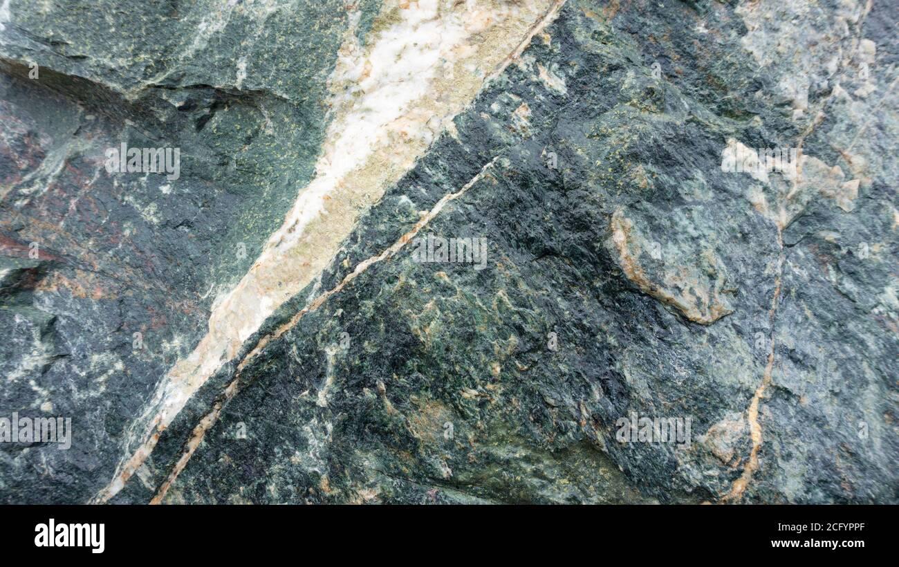 Fondo gris-verde abstracto con textura de piedra de la diabase de gabbro. Fondo de piedra de gabbro-diabase roca. Cantos rodados en diseño paisajístico. Foto de stock