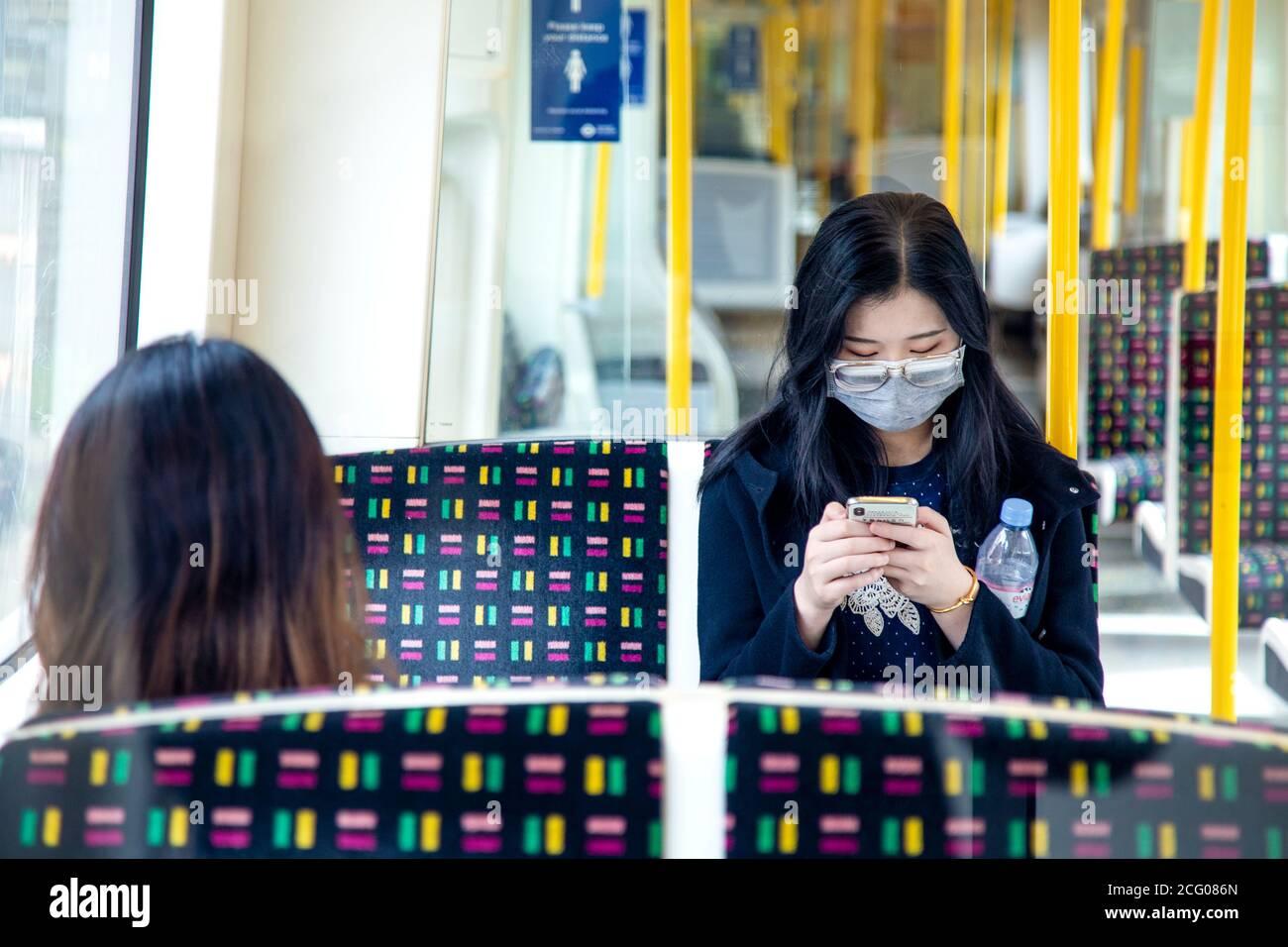 7 de septiembre, Londres, Reino Unido - una mujer asiática sentada en el tubo en un carro vacío de la línea Metropolitana usando máscara facial durante la pandemia del Coronavirus Foto de stock