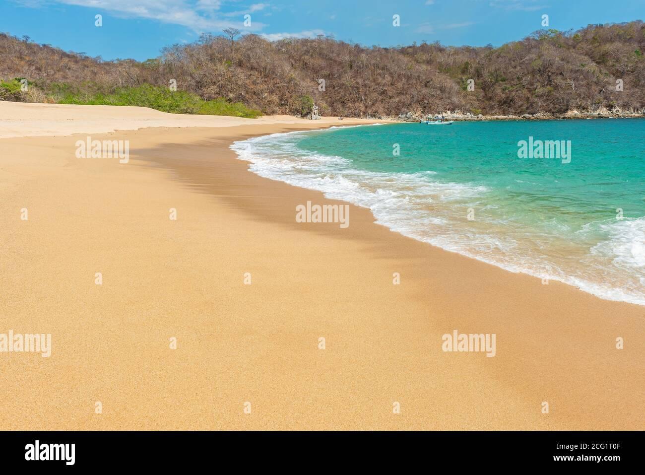 Vista clásica de la bahía y la playa en el complejo turístico Huatulco junto al Océano Pacífico durante el día en el estado de Oaxaca, México. Enfoque en la onda. Foto de stock