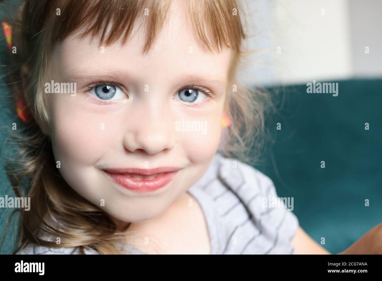 Retrato de niña con ojos azules y una sonrisa leve Foto de stock