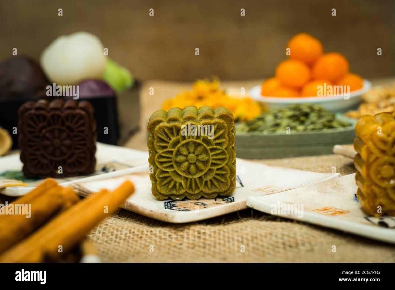 Pastel de luna de mediados de otoño, comida colorida y bebida sobre fondo de las erucas. Viaje, vacaciones, concepto de comida Foto de stock
