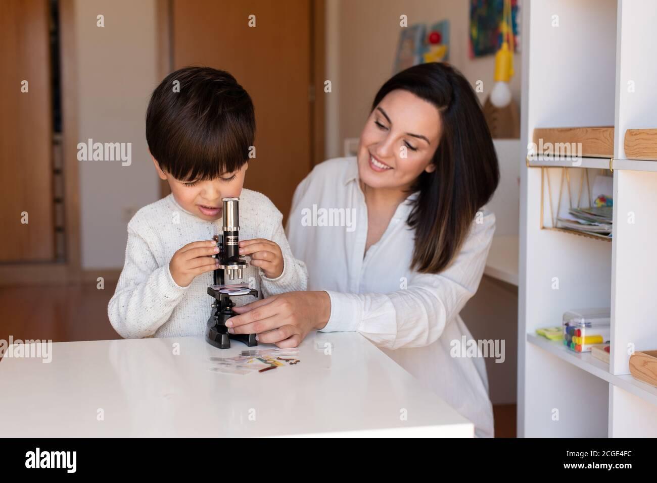 Lillte Kid explorando la ciencia con un microscopio y ayuda de madre o maestro. Resolución de problemas en casa. Comunidad de aprendizaje. Escuela Montessori Foto de stock