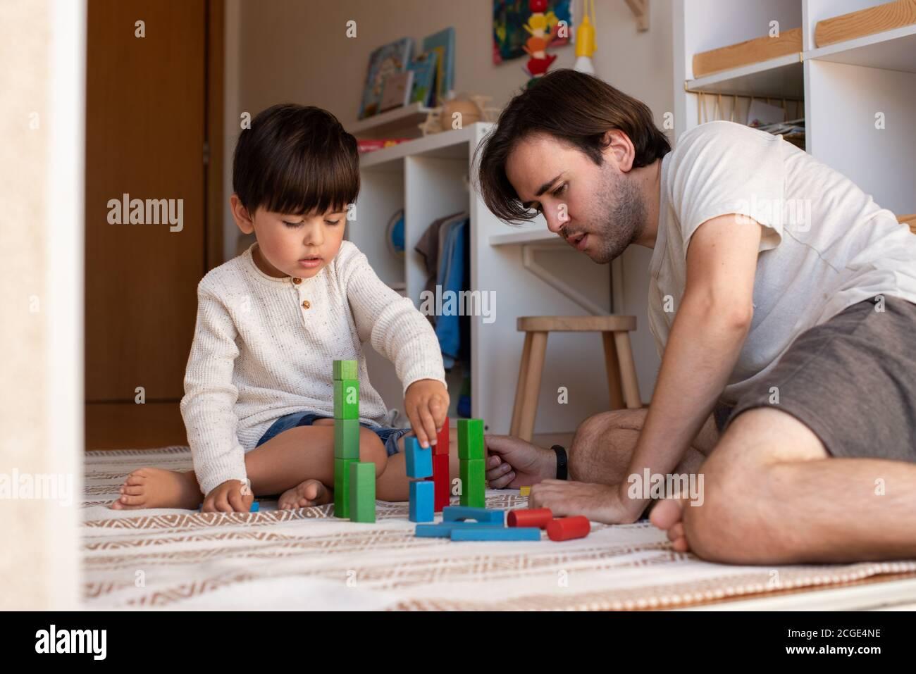 Niño pequeño y su padre jugando en casa con bloques de madera. Homeschooling. Quédate en casa. Tiempo en familia Foto de stock