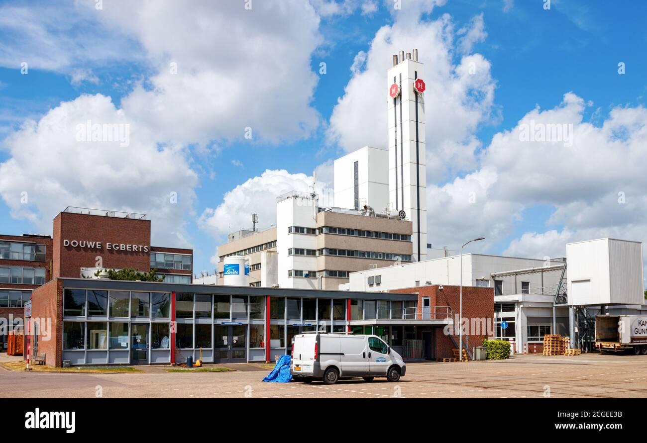 Edificios de oficinas y la chimenea de la planta de café Jacobs Douwe Egberts bajo un cielo azul con nubes. Utrecht, países Bajos. Foto de stock