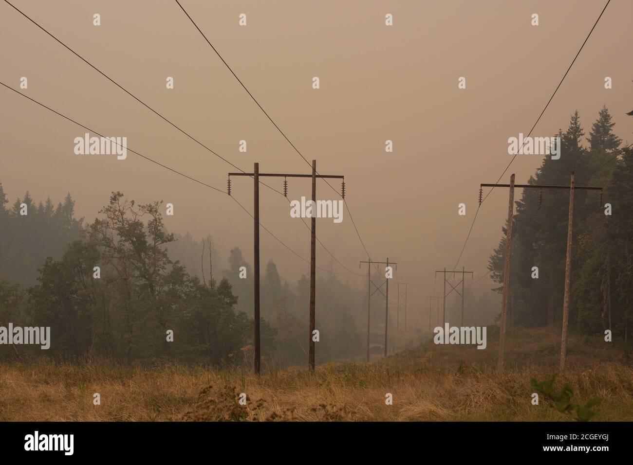 Líneas eléctricas en humo espeso de incendios forestales cercanos, en Eugene, Oregon, EE.UU. Foto de stock