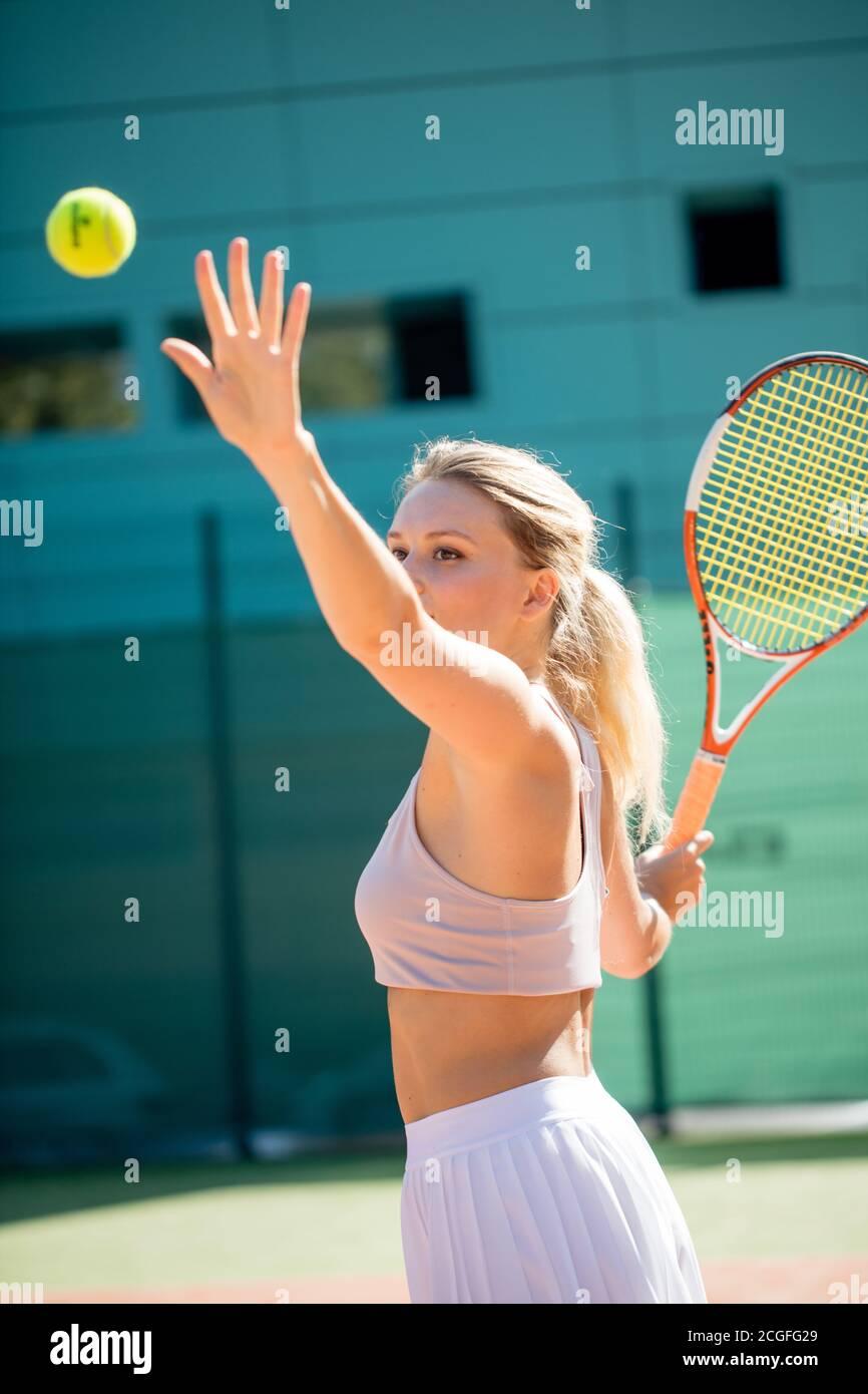 Chica atlética deportiva vistiendo ropa de tenis deportes de verano sirviendo la pelota en juego de tenis en el tribunal exterior. Foto de stock