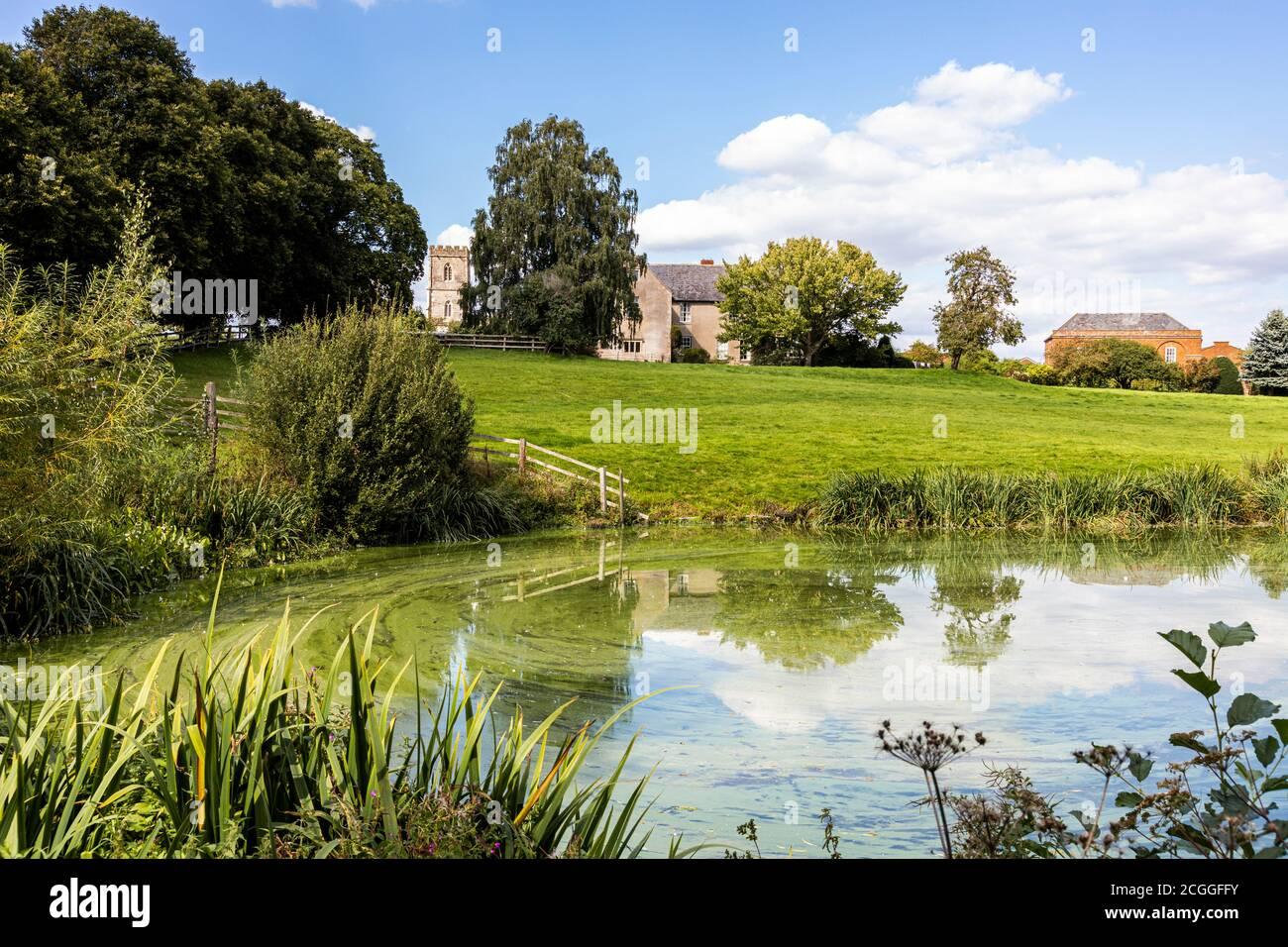 La corte de Maisemore y la iglesia de St Giles vistas a través del lago en el pueblo de Severn Vale de Maisemore, Gloucestershire, Reino Unido Foto de stock