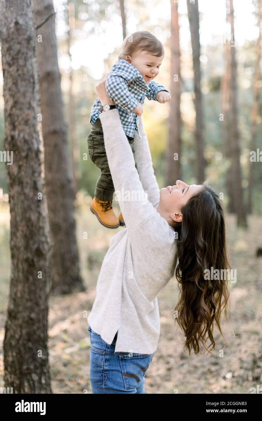 Retrato de feliz madre caucásica levantándose y jugando con su lindo hijo, disfrutando de su paseo conjunto en el bosque de pinos juntos. Feliz familia Foto de stock