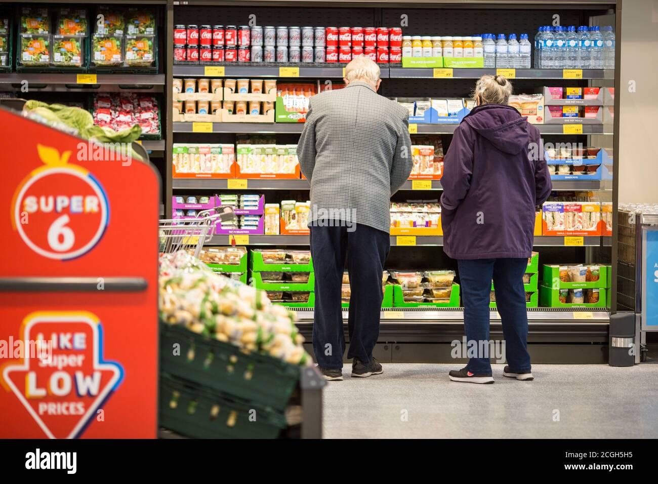 Interior del supermercado Aldi. Una pareja haciendo sus compras Foto de stock