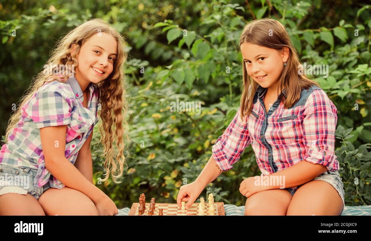 Lluvia de ideas. Hacer que el cerebro funcione. El desarrollo de la primera infancia. dignos adversarios. Desarrollar habilidades ocultas. concentra las niñas juegan al ajedrez. juego de ajedrez hermanas niños calificados. Encienda su cerebro. Foto de stock
